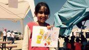 Una bambina con i suoi disegni nel campo profughi